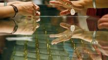A customer in a Beijing gold shop tries on a gold ring. (DAVID GRAY/REUTERS)