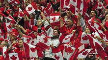 Fans wave flags before Canada's hockey match against the United States at the Vancouver Olympics on February 21, 2010.