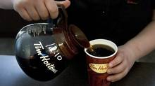 An employee pours a cup of Tim Hortons coffee. (Chris Young/The Canadian Press)
