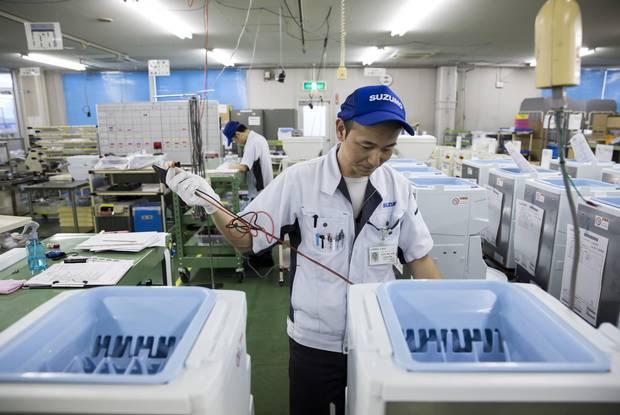 An employee inspects a compact sushi-making machine.