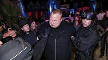 "Actors in police costume mock-arrest Megaupload founder Kim Dotcom, as he launches his new file sharing site ""Mega"" in Auckland January 20, 2013. Dotcom, who is fighting extradition to face U.S. charges of internet piracy, has launched a new cloud storage service called ""Mega"" at a function at Dotcom Mansion in Coatsville, Auckland. (NIGEL MARPLE/Reuters)"