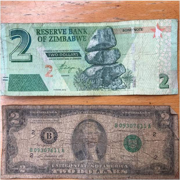 Zimbabwe's official new currency, the 'bond note,' next to a rare U.S. two-dollar note. American currency is much preferred.