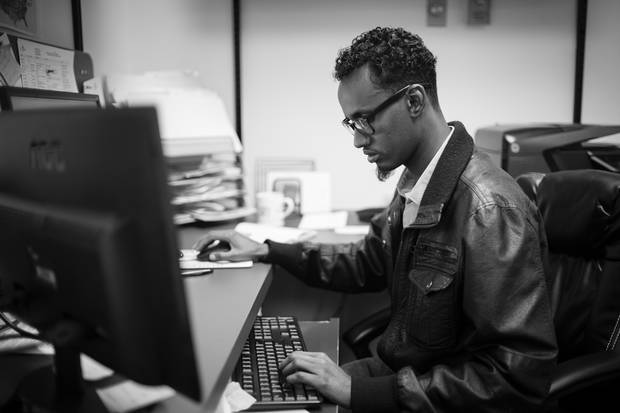 Yahya Samatar, from Somalia, works as a fundraising co-ordinator at Creaddo Group in Winnipeg. He first came to Canada in August 2015, by hiking and swimming north in the Red River. Since then he has been granted refugee status and sends money home to to support his family.
