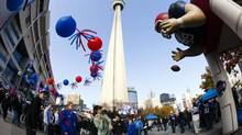 In this file photo, People walk by the CN Tower and the Rogers Centre before the Buffalo Bills play the Washington Redskins in their NFL football game in Toronto, October 30, 2011. The NFL returns to Toronto when the Buffalo Bills play the Atlanta Falcons at the Rogers Centre on Sunday. (MARK BLINCH/REUTERS)