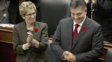 Ontario Premier Kathleen Wynne applauds Finance Minister Charles Sousa after delivering the government's Fall Economic Statement at Queen's Park on Nov. 7, 2013. (MOE DOIRON/THE GLOBE AND MAIL)