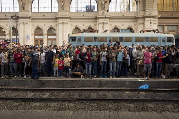 Eager refugees await the arrival of a train at the Keleti train station in Budapest.