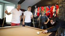 Paul Reinhart, left, and his sons Sam, Griffin and Max keep their competitive spirit stoked with a game of pool at the family home in West Vancouver, B.C. Hockey is more the family business though. Max has been drafted into the NHL and Griffin will follow Friday, while Sam, the youngest, is a couple of years away. (Rafal Gerszak for the globe and mail/Rafal Gerszak)