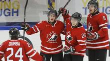 Canada's Curtis Lazar (26) celebrates his goal against Switzerland with teammates Griffin Reinhart (8), Nic Petan and Matt Dumba (L) during the third period of their IIHF World Junior Championship ice hockey game in Malmo, Sweden, January 2, 2014. (Reuters)