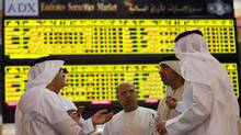 Investors speak in front of a screen displaying stock information at the Abu Dhabi Securities Exchange June 25, 2014. (STRINGER/REUTERS)