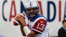 Montreal Alouettes quarterback Anthony Calvillo throws a pass in front of Molson Canadian beer advertisement during the warm-up for aCanadian Football League game in Hamilton, Ontario, Monday, September 5, 2011. (The Canadian Press)