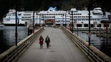Two women walk along a boardwalk at the Horseshoe Bay Ferry Terminal in West Vancouver, B.C. The Queen of Oak Bay is in the background. (DARRYL DYCK For The Globe and Mail)