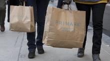 Shoppers carry Primark bags on Oxford Street in London January 17, 2013. (NEIL HALL/Reuters)
