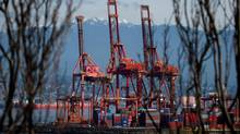 A worker drives past cargo containers stacked beneath cranes at Port Metro Vancouver in Vancouver, B.C., on Thursday March 13, 2014. More than 1,000 container-truck drivers have been on strike since February 26, refusing to work due to low pay and long delays at port terminals. (DARRYL DYCK/THE CANADIAN PRESS)