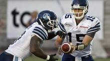 Toronto Argonauts quarterback Ricky Ray hands off to Toronto Argonauts running back Cory Boyd as they face the Montreal Alouettes during first quarter CFL action Friday, July 27, 2012 in Montreal. (Paul Chiasson/THE CANADIAN PRESS)