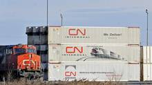 A CN locomotive passes by freight containers at the CN Taschereau yard in Montreal. (GRAHAM HUGHES/THE CANADIAN PRESS)