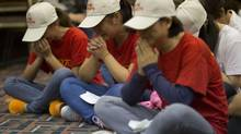 Relatives of Chinese passengers on board the Malaysia Airlines Flight 370 pray at a hotel conference room in Beijing on April 18. (Ng Han Guan/THE ASSOCIATED PRESS)