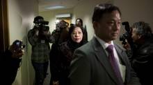 Sap Mui Vong (middle), wife of alleged Asian crime boss Lai Tong Sang, is escorted back to the hearing room after a break in an admissibility hearing at the Immigration and Refugee Board of Canada in Vancouver, February 26, 2013. (Rafal Gerszak for The Globe and Mail)