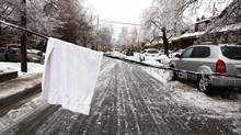 A white towel is placed over a downed powerline to alert passing vehicles after freezing rain in Toronto, Ontario December 22, 2013. Thousands of households are without power in the Greater Toronto area following an overnight ice storm. (HYUNGWON KANG/REUTERS)