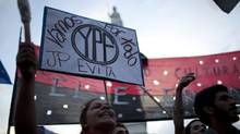 Demonstrators in Buenos Aires on Monday hold up a banner that reads in Spanish 'We are going for all YPF,' in support of a bill proposed by Argentina's President Cristina Fernandez to expropriate 51 per cent of the shares of YPF oil company that is controlled by Spain's Repsol. (Associated Press)
