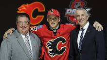 Morgan Klimchuk, a winger, stands with officials from the Calgary Flames sweater after being chosen 28th overall in the first round of the NHL draft, Sunday, June 30, 2013, in Newark, N.J. (Bill Kostroun/AP)
