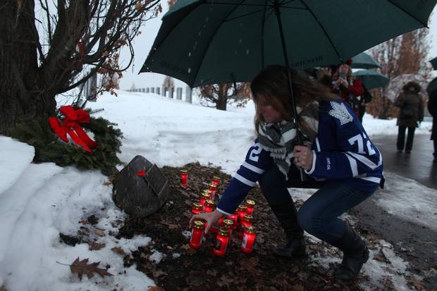 Lisa McBain places a candle for her late brother Corp. John Unrau during a candlelight ceremony to honour the memory of Soldiers of Suicide (S.O.S.) at the National Military Cemetery of the Canadian Forces at Beechwood Cemetery Feb. 21, 2017 in Ottawa.