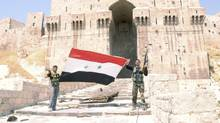 Syrian security personnel show the flag as they stand in front of Aleppo's historic citadel. August 9, 2012. REUTERS/George Ourfalian (SYRIA - Tags: POLITICS CIVIL UNREST MILITARY CONFLICT) (George Ourfalian/REUTERS)