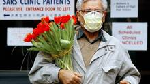 A man wears a protective mask as he carries a bouquet of flowers at Women's College Hospital in Toronto March 28, 2003. Global health officials are closely following a new respiratory virus related to SARS that is believed to have killed at least one person in Saudi Arabia and left another person in critical condition in Britain. (KEVIN FRAYER/THE CANADIAN PRESS)