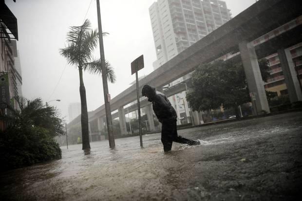 Miami, Sept. 10: A local resident walks across a flooded street.