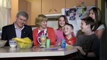 Prime Minister Stephen Harper and his wife Laureen talk with Virginie, 11, Nathan, 6, Jordan, 11 and Demy Pinard, 13 (left to right) during a campaign stop at the Pinard family home in Asbestos, Que., about 150 kilometres east of Montreal, Tuesday April 26, 2011. (Adrian Wyld/The Canadian Press/Adrian Wyld/The Canadian Press)