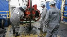 Workers change drilling pipes on the rotary table of a natural gas drilling rig near Towanda, Pa. (TIM SHAFFER/Reuters)