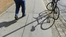 A pedestrian walks by a bike locked to a sign post on King St. West in this file photo. Lisa Ferguson said her bicycle was locked to a pole at the northeast corner of Yonge and Bloor streets, but was gone when she returned (Fred Lum/The Globe and Mail)