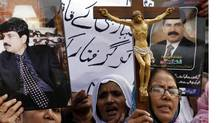 Christian women hold pictures of slain Pakistani Minister of Minorities Shahbaz Bhatti. (ATHAR HUSSAIN/REUTERS)