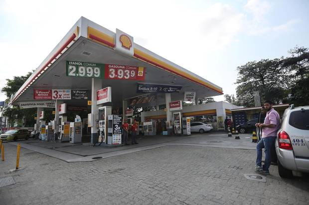 People gather at the Shell gas station where the incident took place.