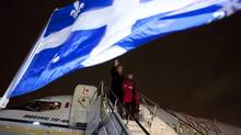 Liberal Leader Michael Ignatieff and his wife Zsuzsanna Zsohar wave as they get off their campaign plane in Montreal. (Jonathan Hayward/The Canadian Press)