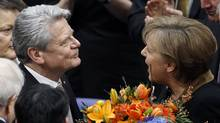 German Chancellor Angela Merkel, right, hands over a bunch of flowers to new elected German President Joachim Gauck, left, at the parliament building Reichstag in Berlin, Germany, Sunday, March 18, 2012. (Michael Sohn/AP/Michael Sohn/AP)