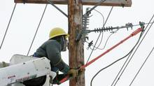 Nova Scotia Power line technician Ken Beck works on repairing a line in Halifax on Tuesday, Nov. 16, 2004 that was damaged during the first winter storm of the season. (Darrell Oake/CP)
