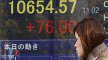 A woman walks by an electronic stock board of a securities firm in Tokyo, Thursday, Jan. 10, 2013. (Koji Sasahara/AP)