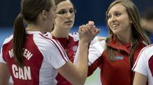 Team Canada's skip Rachel Homan, right, celebrates with third Emma Miskew, left, and lead Lisa Weagle, after her shot in the sixth end against Alberta in the finals match at the Scotties Tournament of Hearts curling championships Sunday, February 9, 2014 in Montreal. (Ryan Remiorz/THE CANADIAN PRESS)