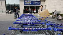 Shoppers emerge from a Wal-Mart Supercenter branch in Beijing October 17, 2006. (CLARO CORTES IV/REUTERS)