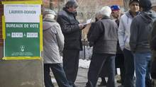 People wait in line to vote at a polling station in Montreal Monday, April 7, 2014 on election day in Quebec. (Graham Hughes/THE CANADIAN PRESS)