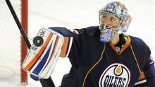 Edmonton Oilers goalie Nikolai Khabibulin deflects a shot from the Minnesota Wild during first period NHL hockey action in Edmonton on Thursday, October 20, 2011. (John Ulan/THE CANADIAN PRESS)