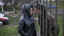 Urij Alexejchuk, a member of the Ukrainian air force, kisses his wife, Sveta, through the perimeter fence of a Ukrainian air force base, which is blockaded by pro-Russian forces, at in Lubimovka, a town in the Crimean region of Ukraine, March 17, 2014. On Monday, the parliament of the breakaway republic of Crimea declared independence, formally asking Russia to annex it and moving swiftly to cement the rupture with the central government in Kiev. (URIEL SINAI/NYT)