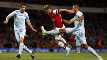 Arsenal's Andrey Arshavin (C) is challenged by Coventry City's Reece Brown during their English League Cup soccer match at the Emirates Stadium in London September 26, 2012. (STEFAN WERMUTH/REUTERS)