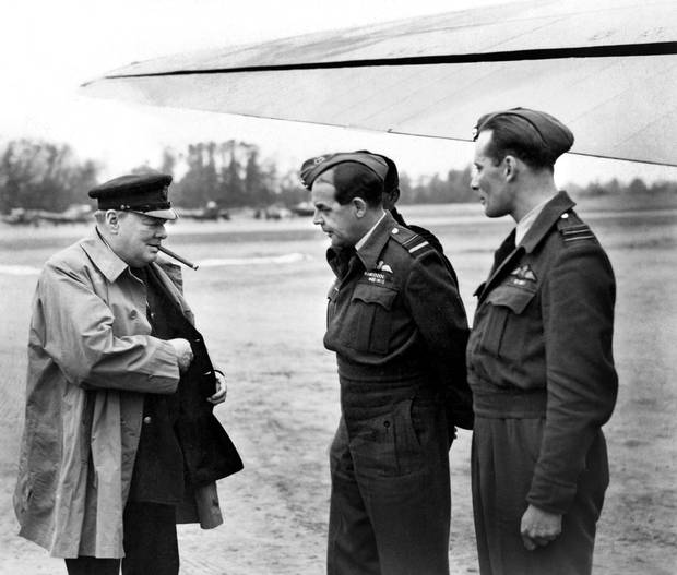Winston Churchill looks for a match to light his trademark cigar while visiting RCAF 414 Squadron at a Normandy airfield in 1944.