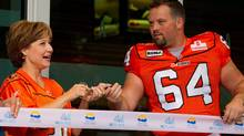 British Columbia Premier Christy Clark, left, and B.C. Lions' Angus Reid take part in a ribbon cutting to officially open the renovated B.C. Place stadium before the Lions played the Edmonton Eskimos in a CFL football game in Vancouver, B.C., on Friday September 30, 2011. The stadium was closed for 18-months to undergo a $563-million renovation which included a new retractable fabric roof. THE CANADIAN PRESS/Darryl Dyck (Darryl Dyck/CP)