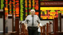 A Filipino trader walks in front of an electronic board during trading at the Philippine Stock Exchange at the financial district of Makati, south of Manila, Philippines, on Tuesday, Aug. 7, 2007. (AARON FAVILA/AP)