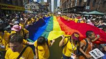 Participants hold a giant pride flag as they take part in the Gay Pride Parade in Toronto, July, 3, 2011. (Mark Blinch/Reuters/Mark Blinch/Reuters)