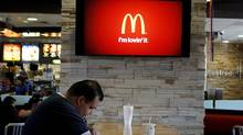 Customer Steven Price sits at a table near a HDTV screen showing the new McDonald's Channel at a McDonald's restaurant in Norwalk, California in this file photo taken October 17, 2011. (FRED PROUSER/FRED PROUSER/REUTERS)