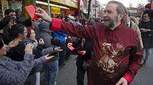 NDP leader Thomas Mulcair hands out red packets during the Chinese New Year parade in Vancouver, British Columbia February 17, 2013. According to the Chinese zodiac, the Lunar New Year began on February 10 and marks the start of the Year of the Snake. (BEN NELMS/REUTERS)