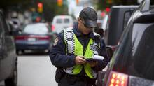 VPD constable Alex Chow pulls over drivers caught on their cell phones on Hornby Street in Vancouver, British Columbia on September 5, 2013. The B.C government, ICBC and the police are launching a month long campaign to prevent distracted driving across the province. (Ben Nelms For The Globe and Mail)